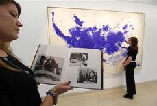 """<p>На фоне картины Ива Кляйна """"ANT 93, Le Buffle"""" (""""Буйвол"""") девушка показывает книгу, где рассказывается история создания полотна, Лондон 4 марта 2010 года. Одна из знаменитейших работ французского художника Ива Кляйна, созданная при помощи голых моделей, облитых синей краской, будет выставлена на продажу на аукционе Christie's в Нью-Йорке в мае, сообщила компания в четверг. REUTERS/Suzanne Plunkett</p>"""