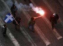 <p>Демонстранты несут по улице флаг Греции, 6 февраля 2010 года. Большинство греков недовольны правительственной программой по сокращению госрасходов, показал опубликованный в пятницу опрос, проведенный компанией Public Issue по заказу телекомпании Skai TV. REUTERS/Stringer</p>