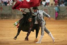"""<p>Spanish bullfighter Cayetano Rivera sports a costume made especially for him by Italian designer Giorgio Armani as he performs a pass to a bull during a """"Corrida Goyesca"""" bullfight in Ronda, southern Spain, September 5, 2009 file photo. REUTERS/Jon Nazca</p>"""