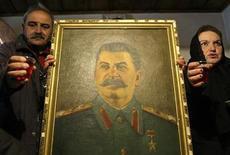 <p>Comunistas hacen un brindis mientras sostinen un retrato del líder soviético Josef Stalin, en Gori, oeste de Tiflis. Marzo 5 2010. Los comunistas rusos rindieron el viernes homenaje al líder soviético Josef Stalin, mientras los liberales acusaban al Kremlin de connivencia para encubrir al dictador. REUTERS/David Mdzinarishvili</p>