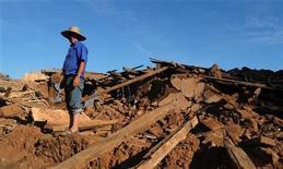 <p>Выживший после землетрясения стоит рядом с разрушенным домом в Каукенесе, Чили 10 марта 2010 года. Новое землетрясение силой 7,2 балла по шкале Рихтера произошло в четверг в Чили, сообщила геологическая служба США. REUTERS/Maglio Perez</p>
