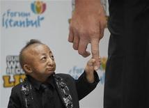 <p>Самый маленький человек в мире Хэ Пинпин (слева) держится за палец самого высокого человека Салтана Косина из Турции в Стамбуле 14 января 2010 года. Самый маленький человек по версии Книги рекордов Гиннесса китаец Хэ Пинпин, ростом всего 74 сантиметра, умер в возрасте 21 года из-за проблем с сердцем. REUTERS/Osman Orsal</p>