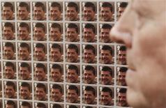 <p>Roger Bacon, father of British Army Major Matthew Bacon, who was killed in Basra, Iraq in 2005, poses with images of his son in a project by artist Steve McQueen at a press preview at the National Portrait Gallery in London March 18, 2010. REUTERS/Luke MacGregor</p>