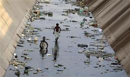 <p>Angola, bambino cammina nell'acqua inquinata del canale. Foto d'archivio. REUTERS/Amr Abdallah Dalsh</p>