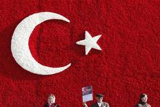 <p>Люди стоят у выложенного гвоздиками флага Турции в Анкаре 10 ноября 2009 года. Турция отказалась поддержать призыв США об ужесточении санкций против Ирана, заявив, что в этом вопросе надо в большей степени использовать дипломатию. REUTERS/Umit Bektas</p>
