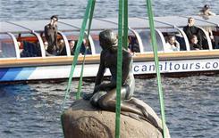 <p>25 marzo 2010. Turisti scattano delle fotografie della Sirenetta prima che venga trasportata a Shanghai. REUTERS/Bob Strong</p>