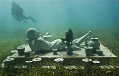 """<p>A diver swims near British artist Jason de Caires Taylor's sculpture """"The Flower of Hope"""" in this undated handout in the Mexican resort of Cancun. At the bottom of its turquoise waters and playing with the reflections of the sun at sea, a series of sculptures were immersed in the Mexican resort of Cancun in what aspires to be a huge underwater museum that harmonizes with the beauty of its coral reefs. REUTERS/Jason de Caires Taylor/Courtesy of Asociados Nauticos de Cancun/Handout</p>"""