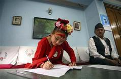 <p>Living Goddess Kumari Chanira Bajracharya takes her School Leaving Certificate exams as exam controller Prakash Subedi (R) looks on at her residence in Patan March 25, 2010. The Living Goddess is taking the exam at her residence as she is not allowed to leave her house other than on 19 religious occasions. REUTERS/Shruti Shrestha</p>