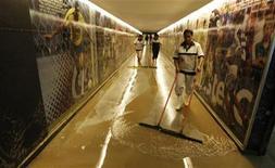 <p>Funcionárias limpam corredor de acesso ao gramado do Maracanã após as chuvas que alagaram o local. 07/04/2010 REUTERS/Bruno Domingos</p>