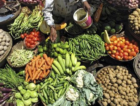 A vendor sprays water on vegetables to keep them fresh at a market in the eastern Indian city of Siliguri July 6, 2009. REUTERS/Rupak De Chowdhuri