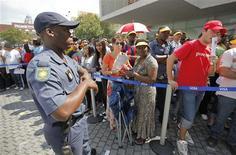 <p>Policiais vigiam fãs ansiosis por ingresso para a Copa do Mundo, em Johanesburgo. Um aposentado morreu nesta quinta-feira na enorme fila que se formou durante a noite para a venda de 500 mil ingressos para a Copa do Mundo na África do Sul, vendidos à vista pela primeira vez.15/04/2010.REUTERS/Mike Hutchings</p>