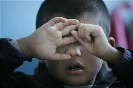 An autistic child reacts during a therapy session at the Stars and Rain School for autistic children in Beijing March 23, 2009. REUTERS/Jason Lee