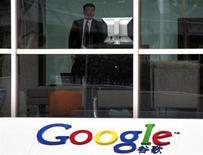 <p>Una guardia di sicurezza guarda dei giornalisti dall'interno della sede di Google China a Pechino REUTERS/David Gray</p>