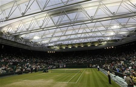 Officials stand on the grass as the roof is closed over Centre Court at the Wimbledon tennis championships, in London June 27, 2009. REUTERS/Eddie Keogh