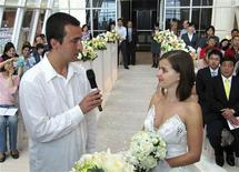 <p>Juraj Hegyi (L), 32, and Zuzana Marcekova, 31, recite their vows during their wedding at a hotel in Taoyuan, northern Taiwan, April 20, 2010. A hotel in Taiwan organized an impromptu wedding for the Slovakian couple who found themselves stranded on the island for six days and unable to get home for their own long-planned ceremony after volcanic ash closed Europe's skies. When Hegyi and Marcekova, were spotted crying in the Orchard Park Hotel near Taiwan's main airport, the manager offered to set up a wedding on site, inviting clergy from a nearby university and packing the venue with 100 people including other stranded Europeans. REUTERS/Stringer</p>