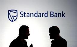 <p>Businessmen chat in front of a Standard Bank logo in Sandton outside Johannesburg October 25, 2007. REUTERS/Siphiwe Sibeko</p>