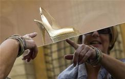 <p>Imagen de archivo de una mujer apuntando a unos zapatos del diseñador Jimmy Choo en una vitrina en Via Condotti, centro de Roma. Oct 7 2008 Los amantes de los zapatos en Londres se han pegado a la pantalla de su ordenador en una carrera para ganar un par de Jimmy Choo gratis. REUTERS/Tony Gentile/ARCHIVO</p>