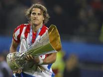 <p>Diego Forlan, do Atlético de Madri, caminha com troféu da Liga Europa após vitória sobre o Fulham. REUTERS/Kai Pfaffenbach</p>