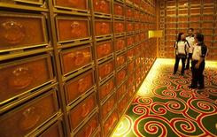 <p>Sales agents talk to a prospective customer about the niches in the Royal Suite at Nirvana Memorial Garden in Singapore May 15, 2010. REUTERS/Edgar Su</p>