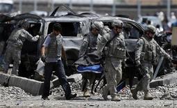 <p>Американские солдаты уносят тело погибшего с места атаки боевика-смертника в Кабуле 18 мая 2010 года. Атака смертника на конвой НАТО в Кабуле унесла как минимум 12 жизней, 47 человек получили ранения, сообщил Рейтер представитель министерства обороны страны Земарай Башари. REUTERS/Ahmad Masood</p>