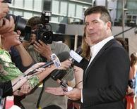<p>Simon Cowell, one of the judges on the American Idol television show, is interviewed as he arrives for the show's season finale in Los Angeles, California, May 21, 2008. REUTERS/Fred Prouser</p>