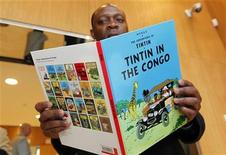 """<p>Congolese-born Bienvenu Mbutu Mondondo holds the """"Tintin in Congo"""" comics ahead of a hearing at the Palace of Justice in Brussels May 12, 2010. REUTERS/Thierry Roge</p>"""