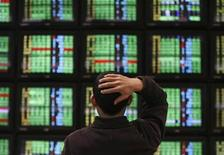 <p>A man looks at stock market prices on computer monitors inside a securities company in Taipei January 15, 2009. REUTERS/Nicky Loh</p>