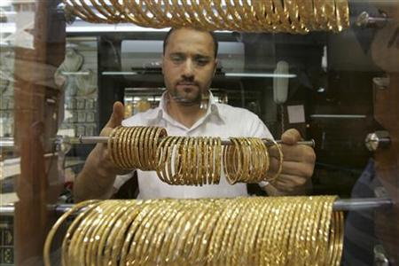 A Jordanian goldsmith holds gold bracelets at his shop in Amman June 9, 2010. REUTERS/Muhammad Hamed