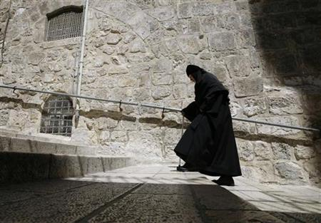 A nun walks in Jerusalem's Old City near the Church of the Holy Sepulchre March 31, 2010. REUTERS/Ammar Awad