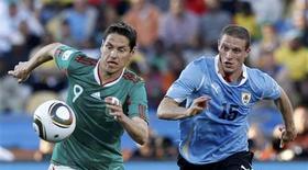 <p>O jogador uruguaio Diego Perez (à direita) luta pela bola com o mexicano Guillermo Franco, em partida pelo Grupo A da Copa do Mundo de 2010 no estádio Royal Bafokeng em Rustemburgo, 22 de junho de 2010. REUTERS/Alessandro Bianchi</p>