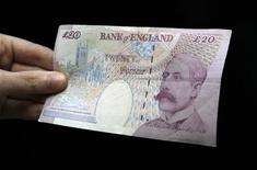 <p>A woman holds a Bank of England twenty pound note with the image of Edward Elgar on one side in Edinburgh, Scotland June 29, 2010 in this posed photograph. REUTERS/David Moir</p>