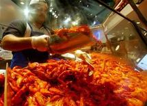 <p>A worker at Sydney's Fish Markets scoops prawns, also known as shrimp, during the Christmas eve dash by Australians for the ocean delicacy. REUTERS/David Gray</p>