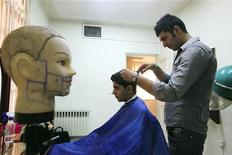 <p>A barber cuts hair at an official hairstyle show in Tehran July 5, 2010. A guide containing pictures of hairstyles considered appropriate for Iranians, which are inspired by the country's culture, religion and Islamic law, was released and approved by Iran's Culture Ministry recently. REUTERS/Mohsen Rezaii/Mehr News</p>