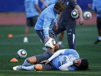 <p>Lugano ajuda Abreu durante treino. O Uruguai terá o capitão e um dos pilares da defesa, Diego Lugano, recuperado para o confronto de sábado contra a Alemanha pelo terceiro lugar da Copa do Mundo, após sua ausência nas semifinais por culpa de uma contusão.09/07/2010.REUTERS/Marcos Brindicci</p>