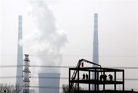 Chimney stacks billow smoke from a coal-burning power station behind construction workers as they lay concrete inside the shell of a new building in Beijing April 8, 2010. REUTERS/David Gray