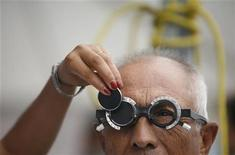 <p>A man receives an eye exam as an ophthalmologist changes a lens during a health campaign in the suburb of Escobedo, in Monterrey June 12, 2008. REUTERS/Tomas Bravo</p>