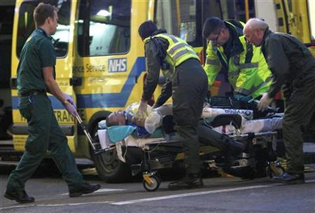 Newspaper seller Ian Tomlinson, 47, who later died, is taken to an ambulance after he became caught up in demonstrations near the Bank of England in London April 1, 2009. REUTERS/Andrew Winning