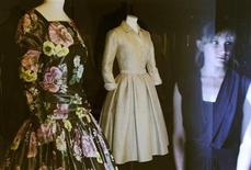<p>An employee is reflected as she poses in front of outfits worn by late actress and Monaco Princess Grace Kelly that form part of an exhibition of the star's wardrobe at the Victoria and Albert Museum in London April 15, 2010. REUTERS/Luke MacGregor</p>