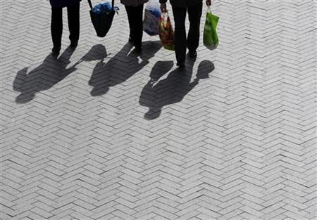 The shadows of shoppers are cast onto the ground in Birmingham, central England March 24, 2009. REUTERS/Darren Staples