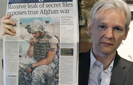 Wikileaks founder Julian Assange holds up a copy of a newspaper during a press conference at the Frontline Club in central London, July 26, 2010. REUTERS/Andrew Winning