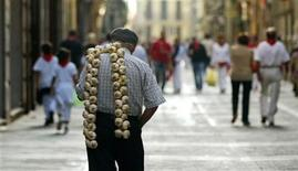 <p>A man carries a string of garlic on his shoulder through the old part of town during San Fermin Festival in Pamplona July 10, 2006. REUTERS/Pablo Sanchez</p>
