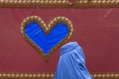 "<p>An Afghan woman walks past a decoration on the side of a traditional ""Reksha"" motor-taxi in Herat November 1, 2009. REUTERS/Morteza Nikoubazl</p>"