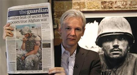 Wikileaks founder Julian Assange holds up a copy of the Guardian newspaper during a press conference at the Frontline Club in central London, July 26, 2010. REUTERS/Andrew Winning