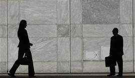 <p>People are silhouetted at Canary Wharf business district in London in a file photo. REUTERS/Luke MacGregor</p>