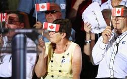 <p>Conservative party supporters use Canadian flags to shield their eyes from bright stage lighting as they wait for the arrival of Prime Minister Stephen Harper at the Forties Community Centre in Forties, Nova Scotia, August 18, 2010. REUTERS/Paul Darrow</p>
