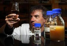 <p>Профессор Мартин Тэнгей держит бокал виски во время презентации биотоплива из виски в Эдинбурге 17 августа 2010 года. Шотландские ученые представили новое биотопливо, сделанное на основе побочных продуктов от производства виски. REUTERS/David Moir</p>