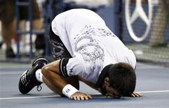 <p>Novak Djokovic of Serbia kisses the court as he celebrates his victory against Roger Federer of Switzerland during the U.S. Open tennis tournament in New York, September 11, 2010. REUTERS/Kevin Lamarque</p>