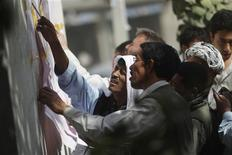 <p>Representatives of candidates check the results in front of a polling station in Kabul September 19, 2010. REUTERS/Andrew Biraj</p>
