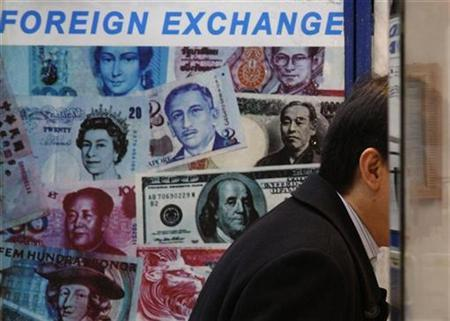 A customer is served at a counter inside a foreign exchange store displaying a poster of various banknotes including the Chinese yuan or renminbi (RMB) in Hong Kong November 20, 2009. REUTERS/Bobby Yip
