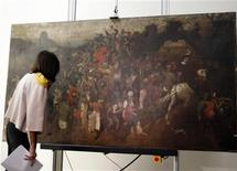 "<p>Spanish Culture Minister Angeles Gonzalez-Sinde looks at ""The Wine of Saint Martin's Day"", a previously unknown work by Pieter Bruegel the Elder, during its exhibition to the media at the Prado museum in Madrid September 23, 2010. The painting has been attributed to Bruegel, who with this painting has only 41 known works, by the Prado museum after several months of study and the restoration of the painting. REUTERS/Andrea Comas</p>"